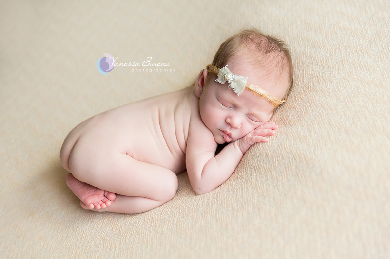 Nouveau-né avec petit noeud beige-doré dans les cheveux