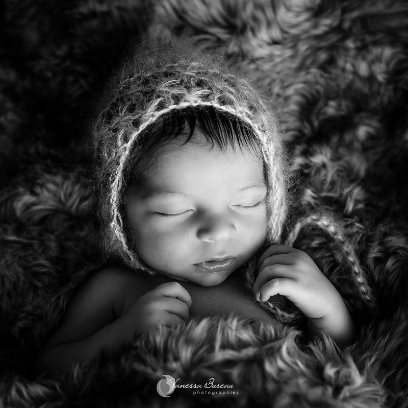 Nouveau-né, photographe Dijon, bébé sur plaid en fourrure, portrait serré en noir et blnac