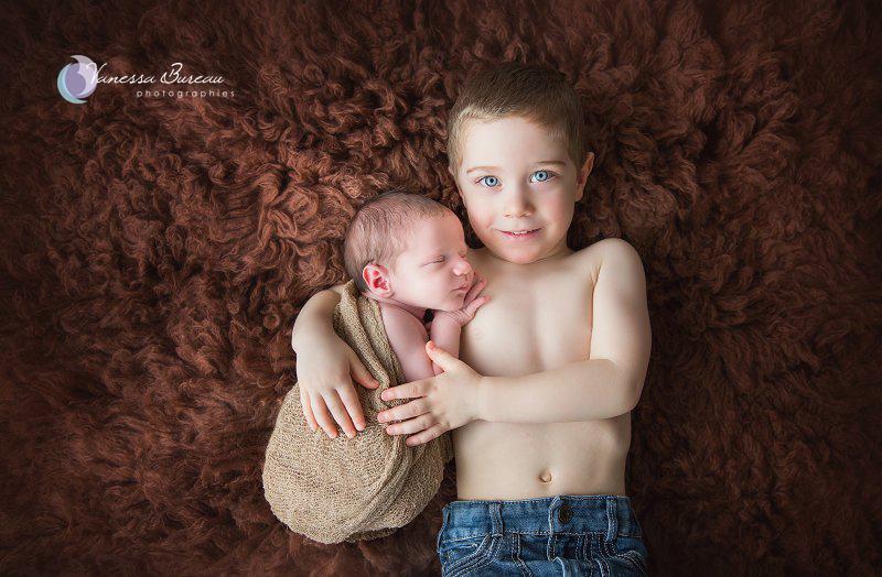 Nouveau-né, photographe Dijon, sur fourrure brune avec son grand frère aux yeux bleus