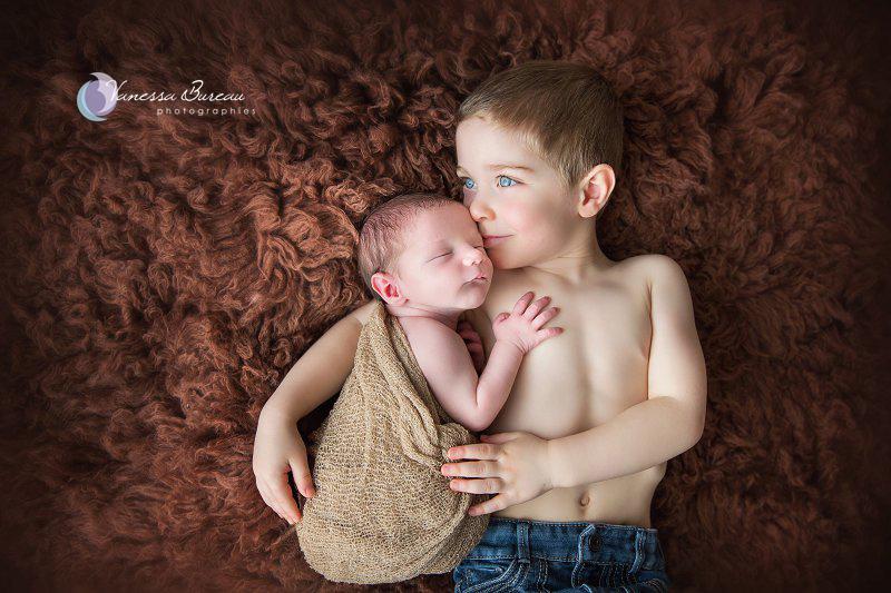 Nouveau-né, photographe Dijon, sur fourrure brune, avec son grande frère aux yeux bleus