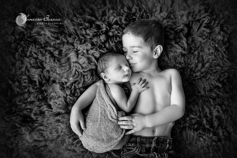 Nouveau-né, photographe Dijon, sur fourrure avec son grand frère qui fait semblant de dormir