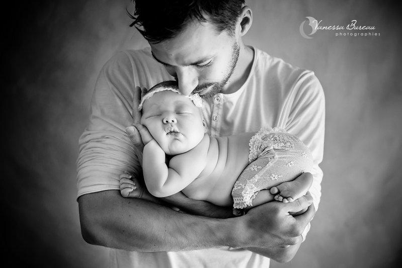 Nouveau-né, photographe Dijon, dans les bras de Papa en noir et blanc