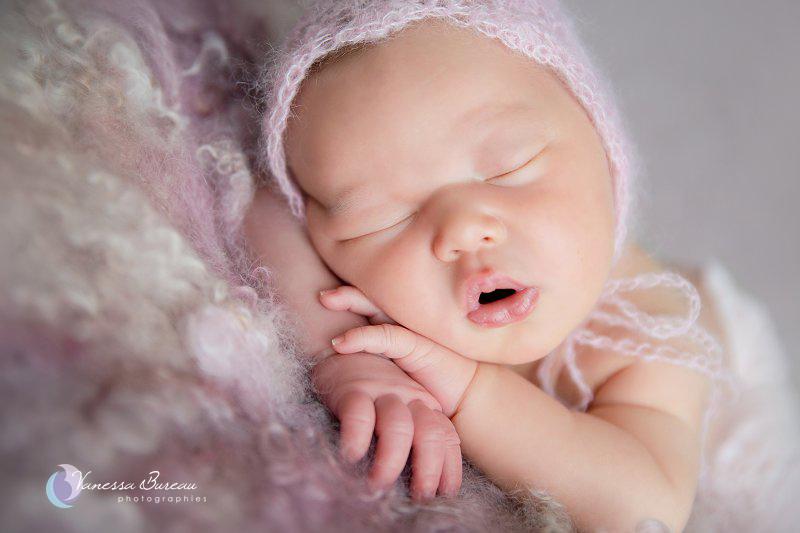 Nouveau-né, photographe Dijon, portrait tête sur les mains avec bonnet, fond laine violet
