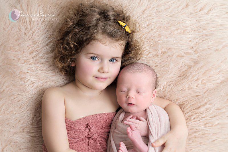 Photo grande soeur cheveux bouclés et nouveau-né