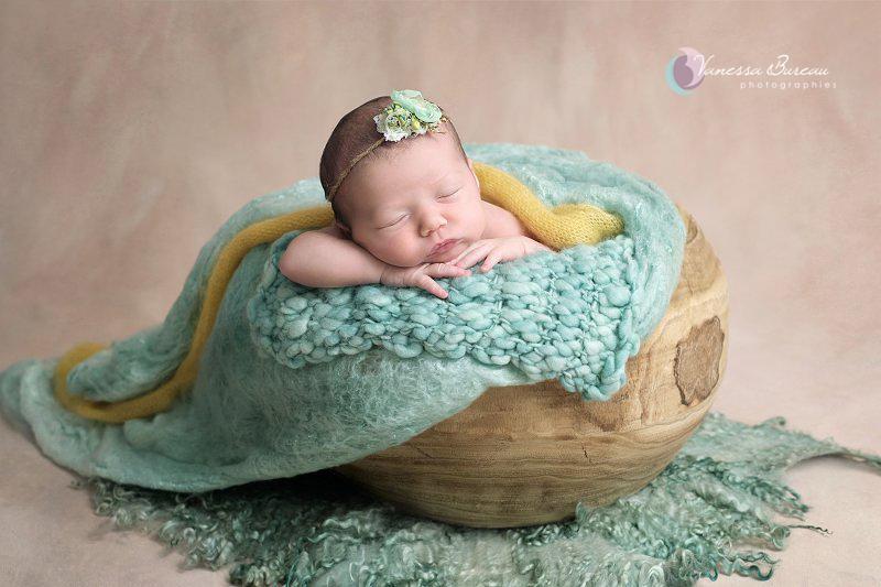 Nouveau-né la tête sur les mains, vert et jaune, panier bois