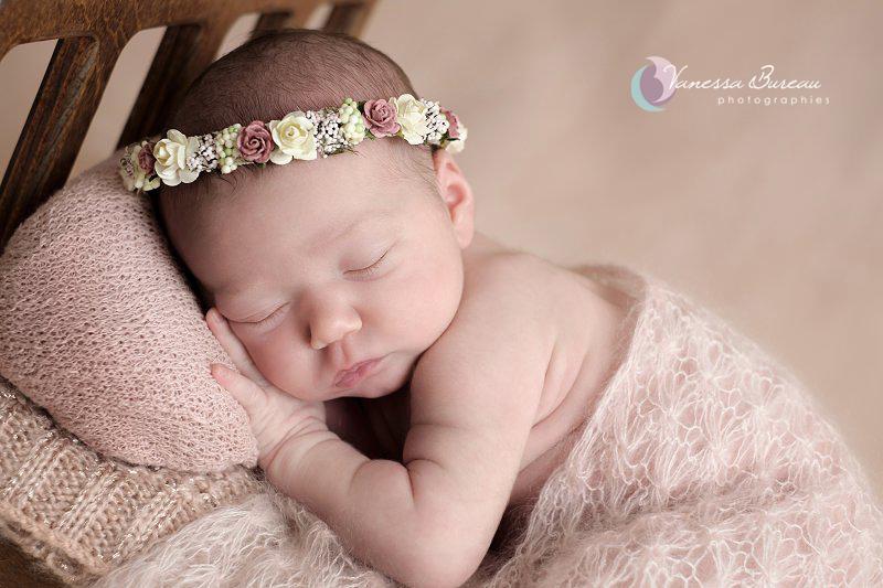 Nouveau-né allongé dans petit lit, couronne de fleur
