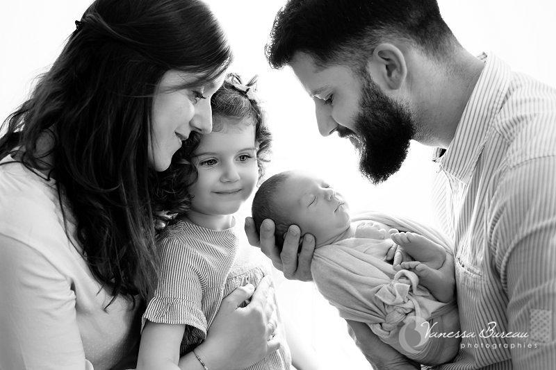 Parents, grande soeur et nouveau-né en contre-jour