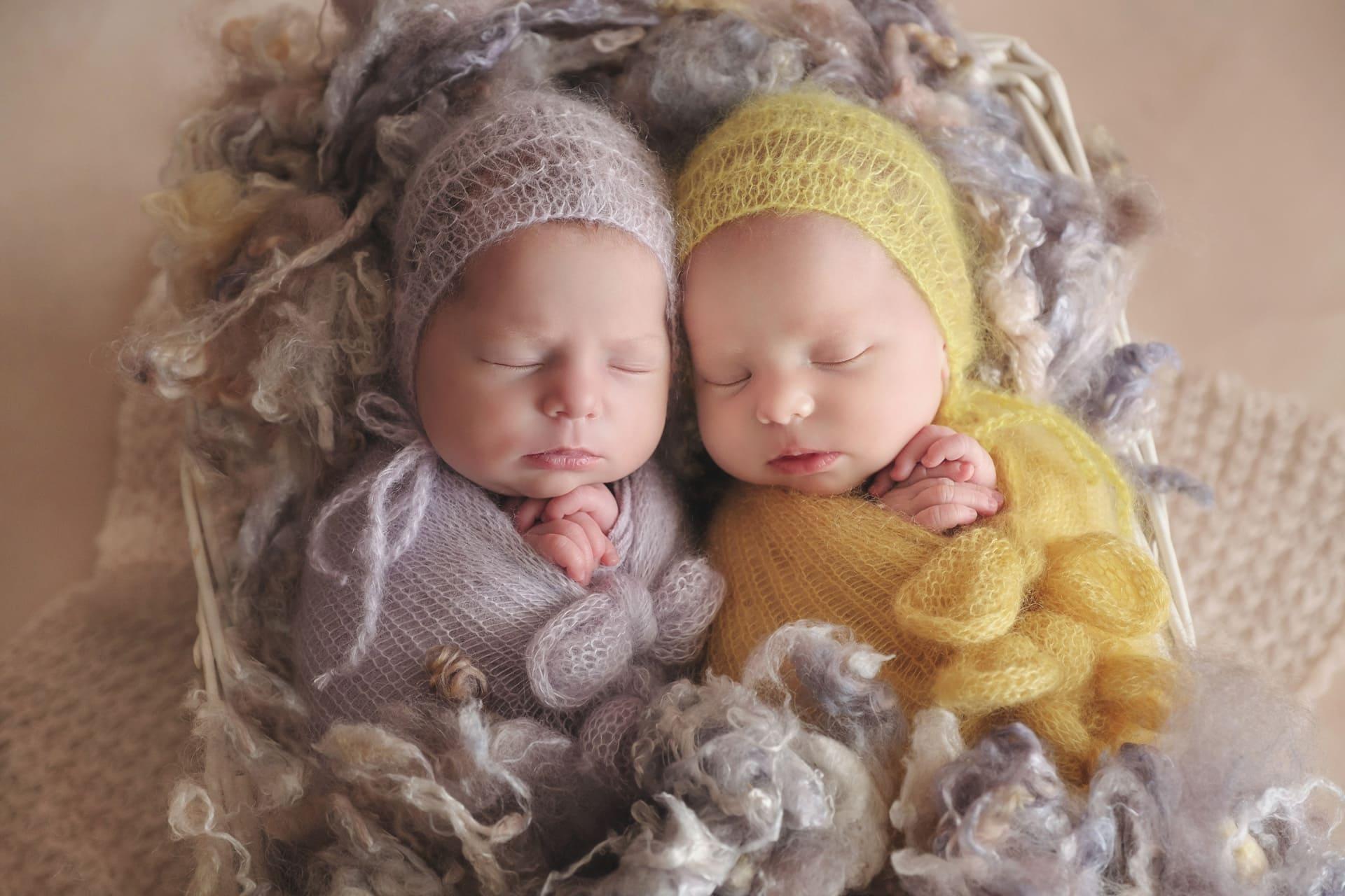 Jumeaux nouveau-né enveloppées dans couverture jaune et violet