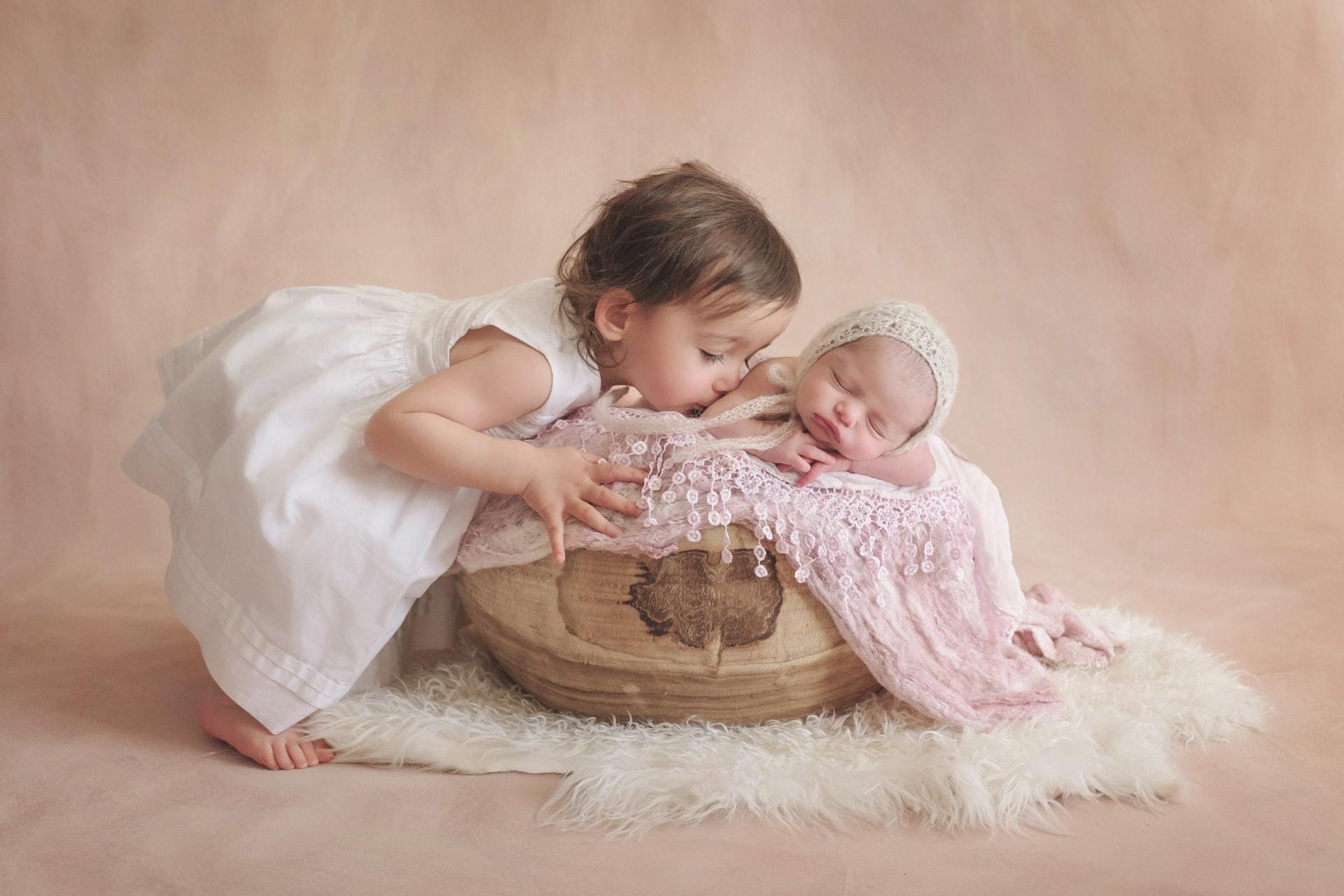 Grande sœur avec nouveau-né chez photographe