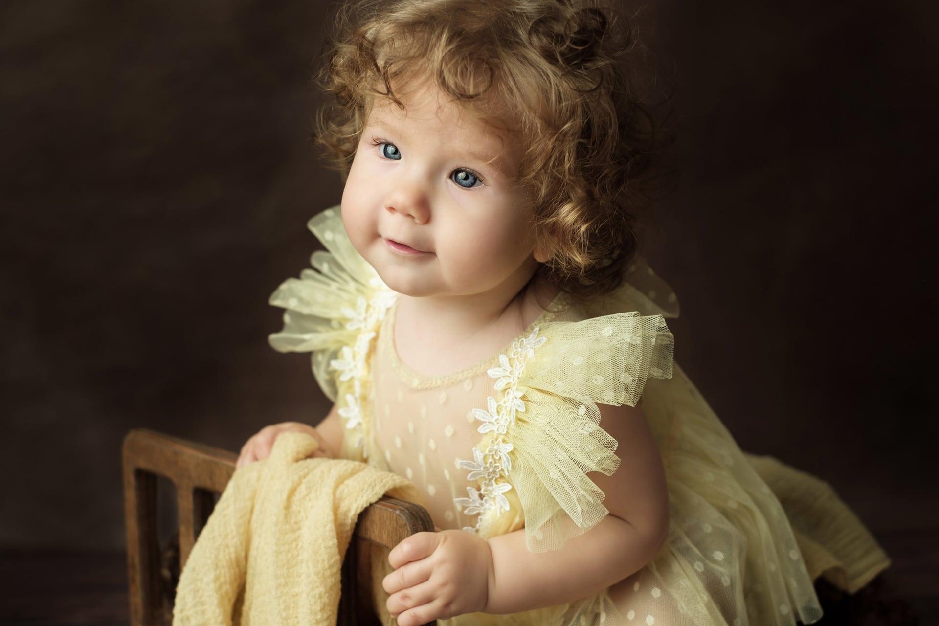 Portrait bébé aux cheveux bouclés et robe jaune
