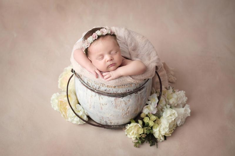 Nouveau-né dans un seau avec des fleurs