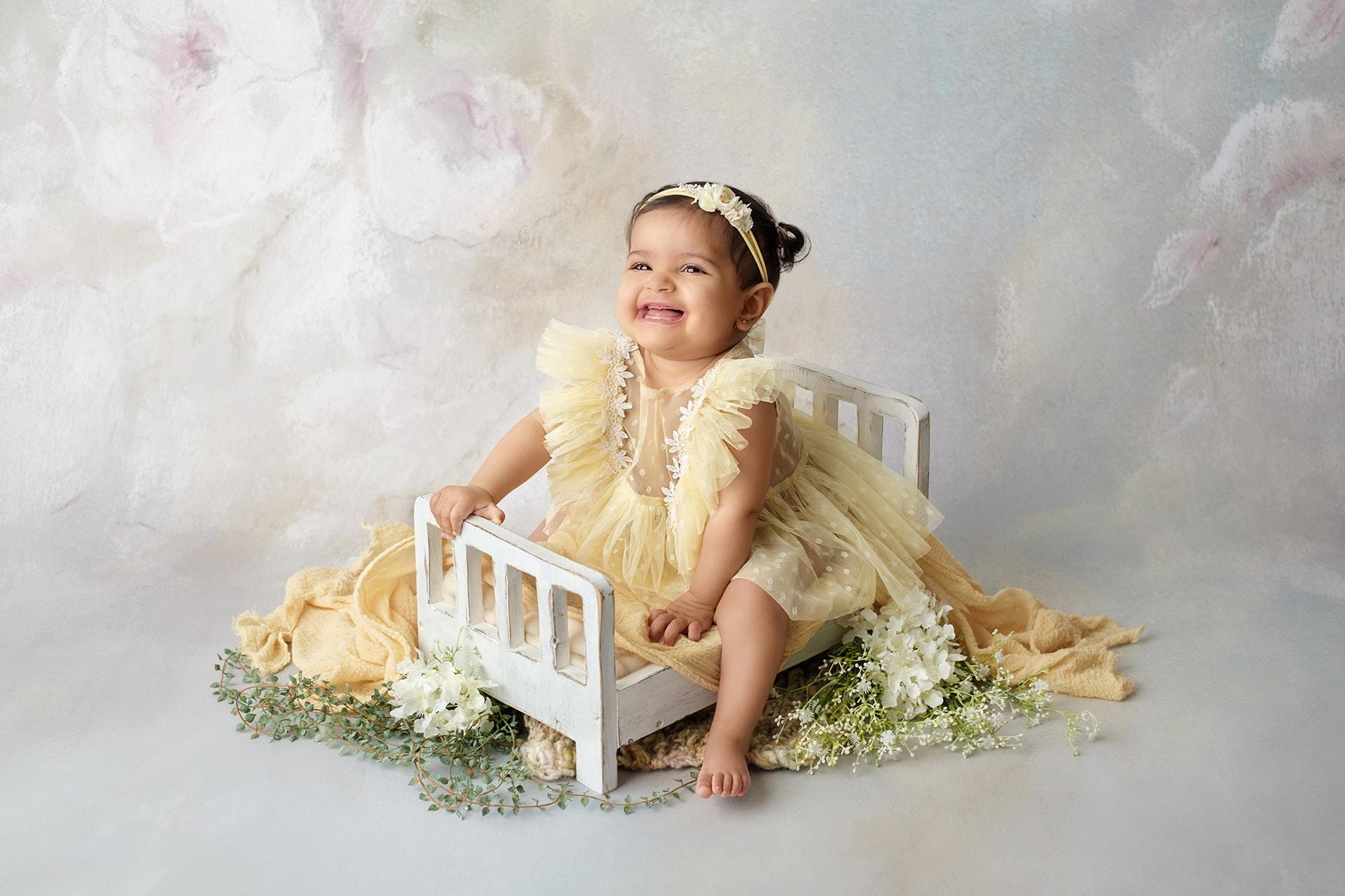 Portrait bébé avec lit en bois et fleurs