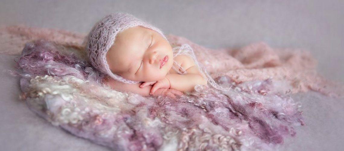 Nouveau-né, photographe Dijon, tête sur les mains, avec bonnet, fond laine violet