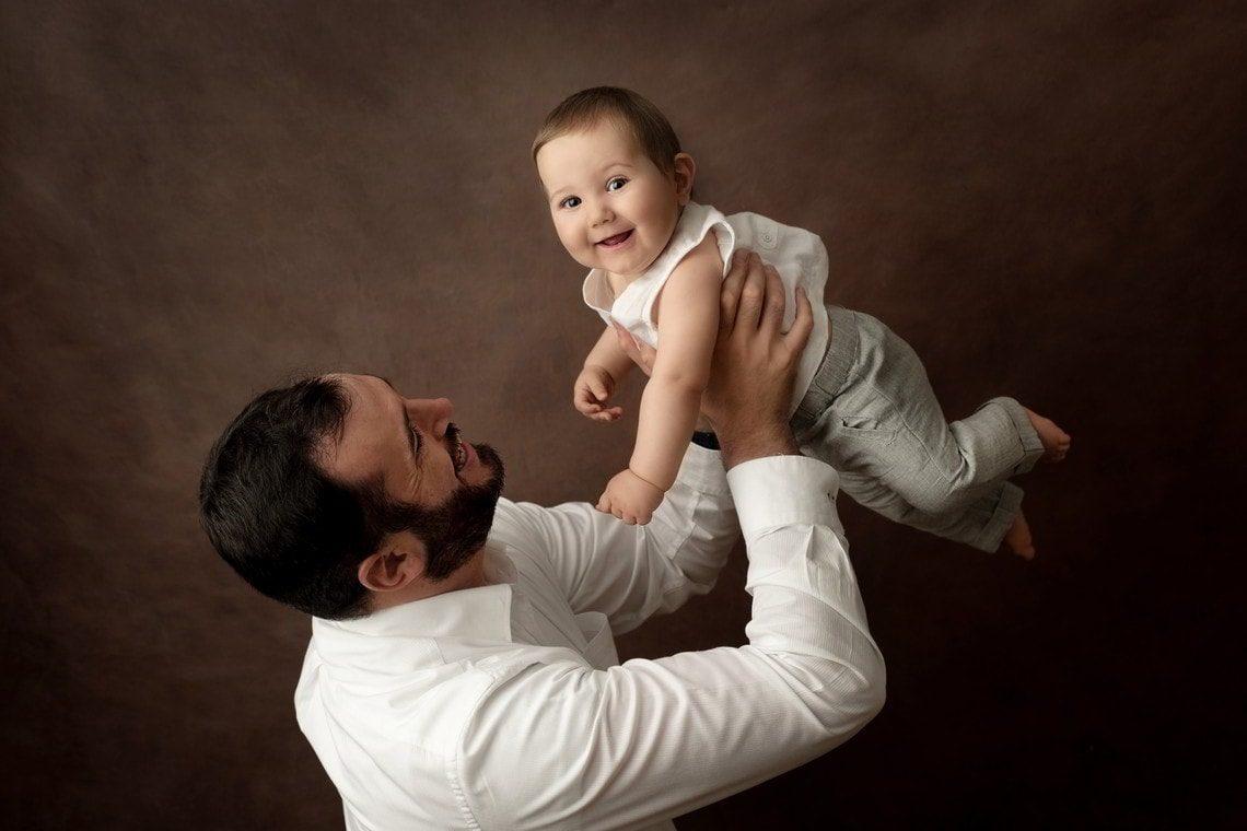 Bébé en l'air dans bras de son papa