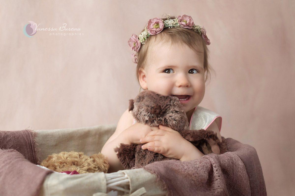 Bébé avec couronne de fleurs, câlin à peluche