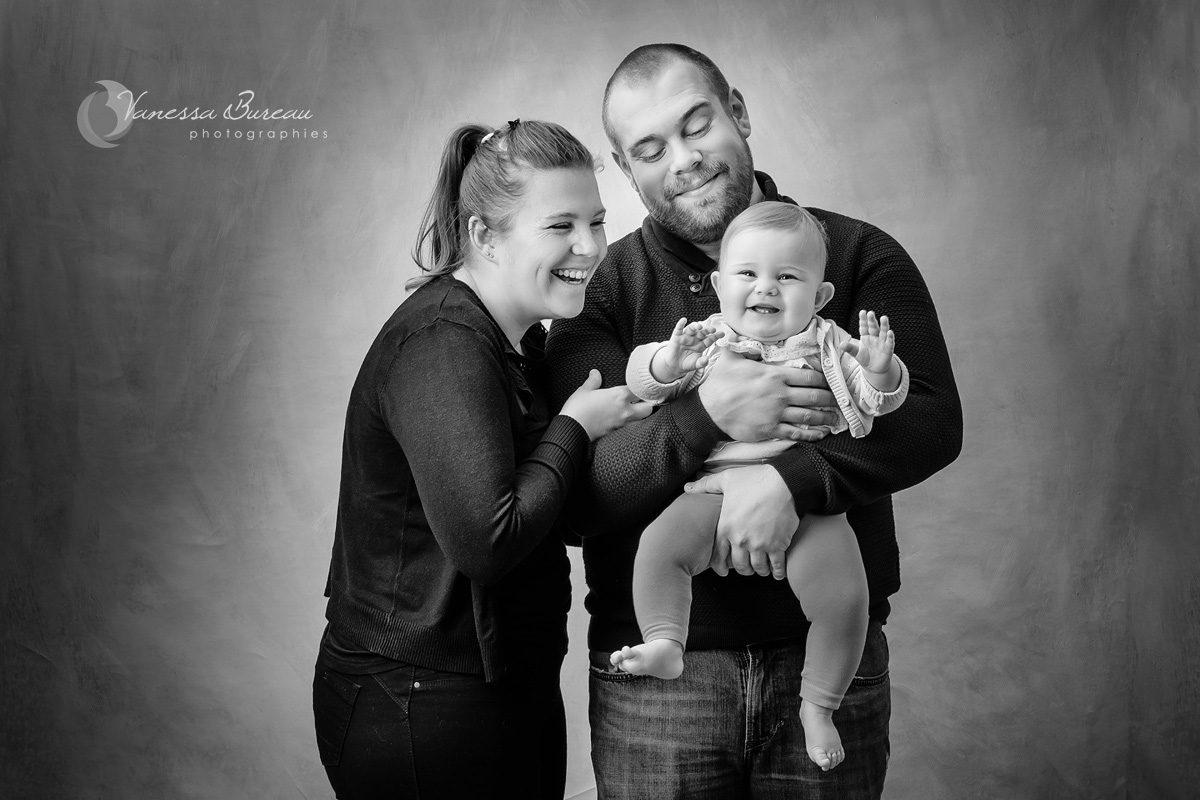 Bébé fille dans bras des parents en noir et blanc