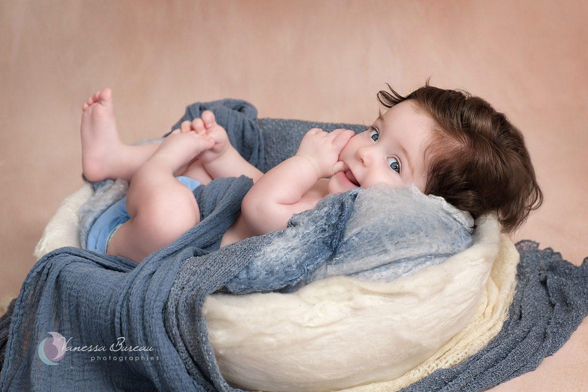 Bébé fille aux cheveux bruns bouclés dans décor bleu