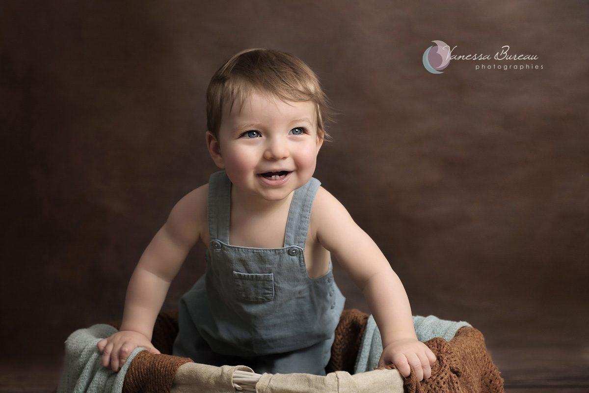 Bébé souriant dans panier avec décor brun