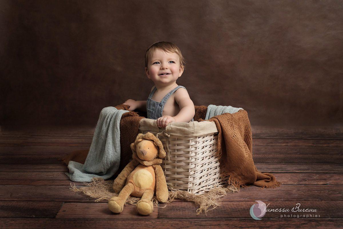 Bébé dans panier avec doudou devant