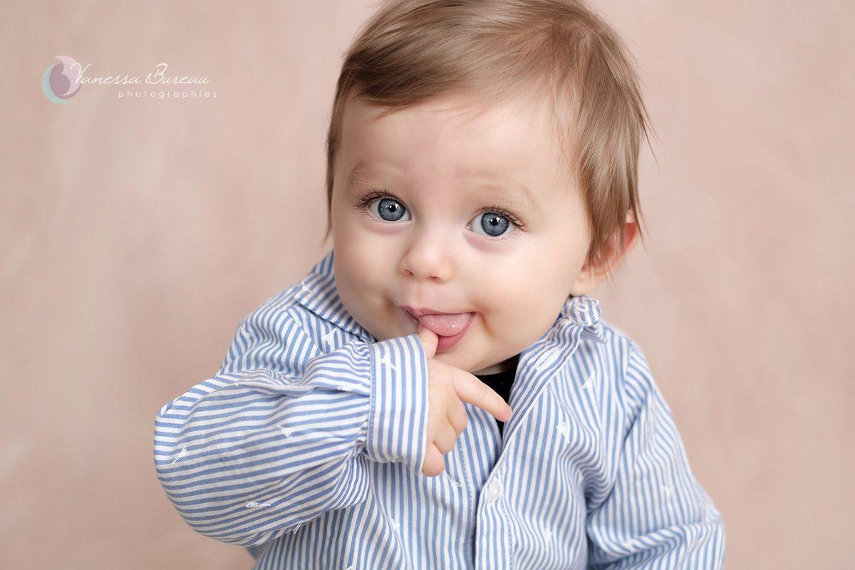 Bébé aux yeux bleus tire la langue