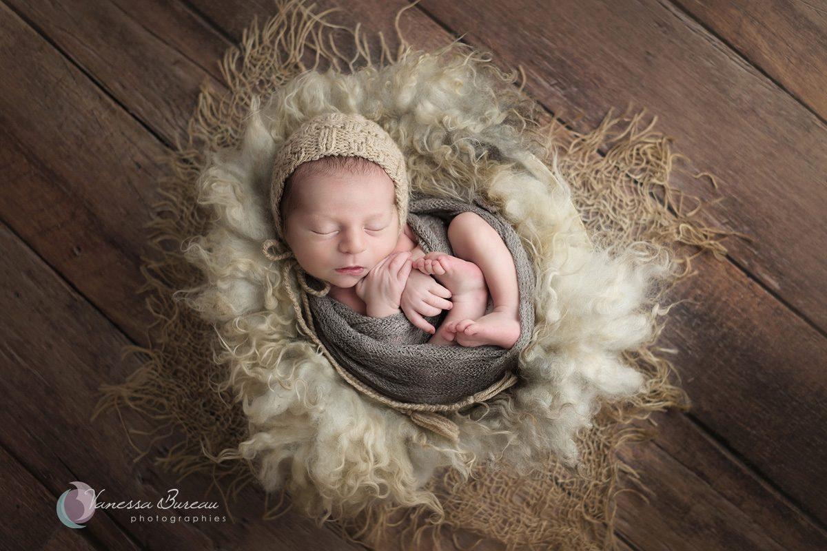 Nouveau-né avec bonnet dans un cocon beige
