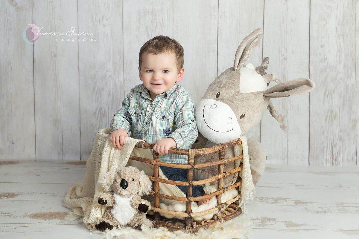 Bébé dans panier en bambou avec peluches