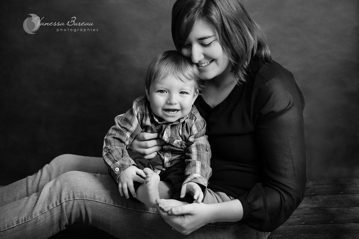 Une maman est assise par terre, avec son petit garçon sur les jambes. Un portrait avec son bébé en noir et blanc réalisé en studio à Dijon.