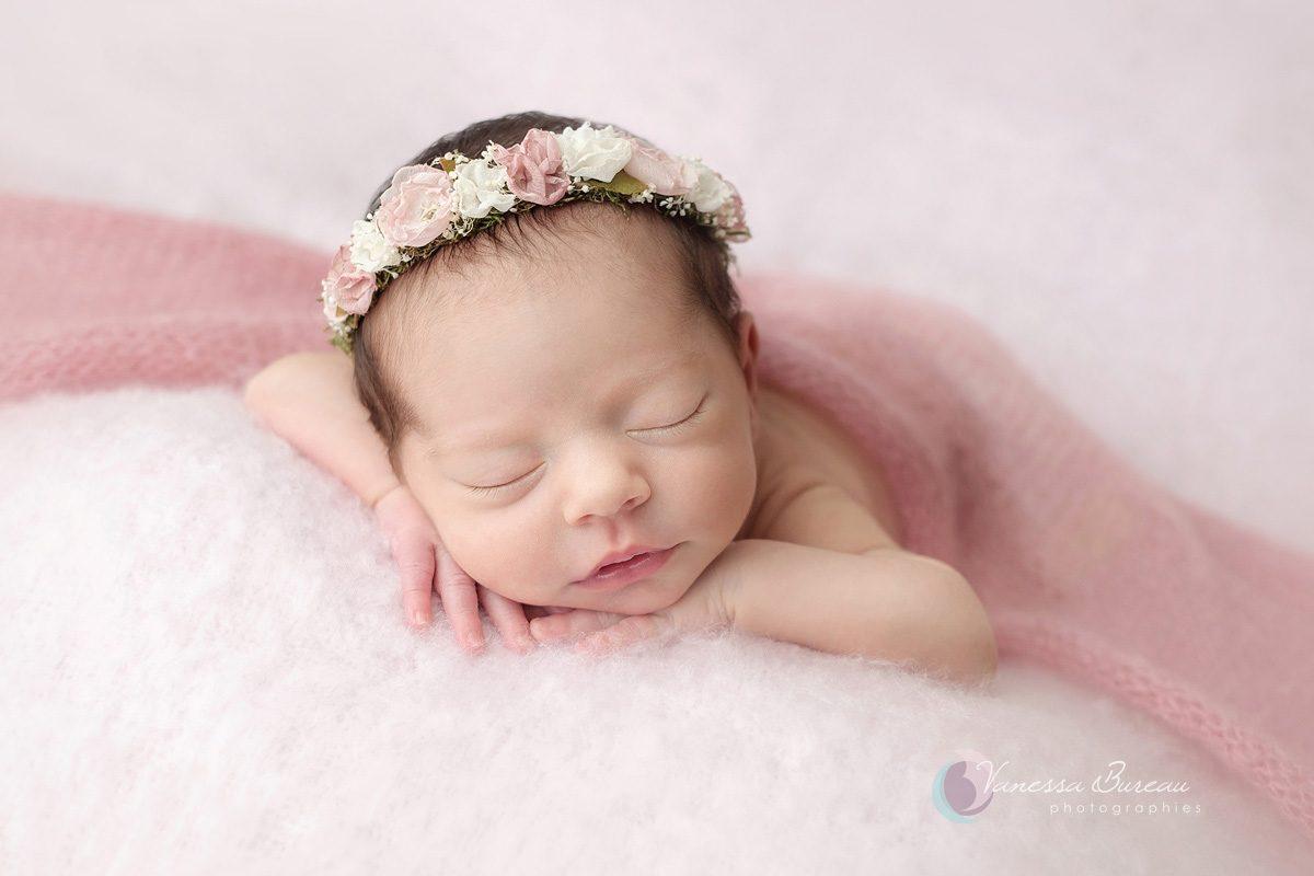 Nouveau-né avec couronne de fleurs roses