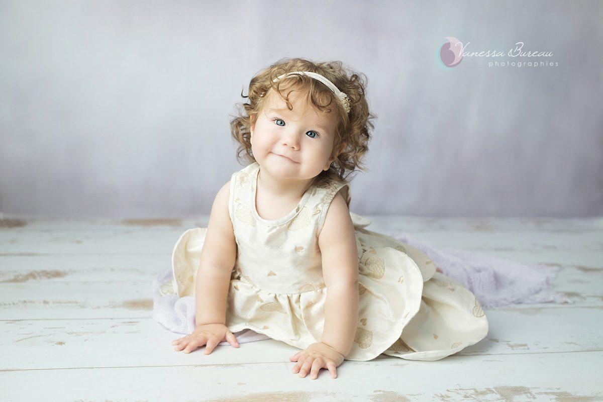 Bébé avec robe dorée et fond violet