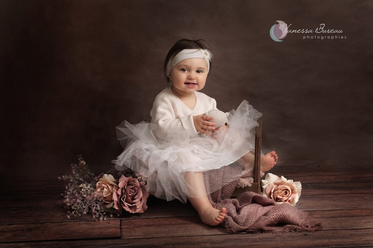 Bébé fille sur lit bois avec fleurs