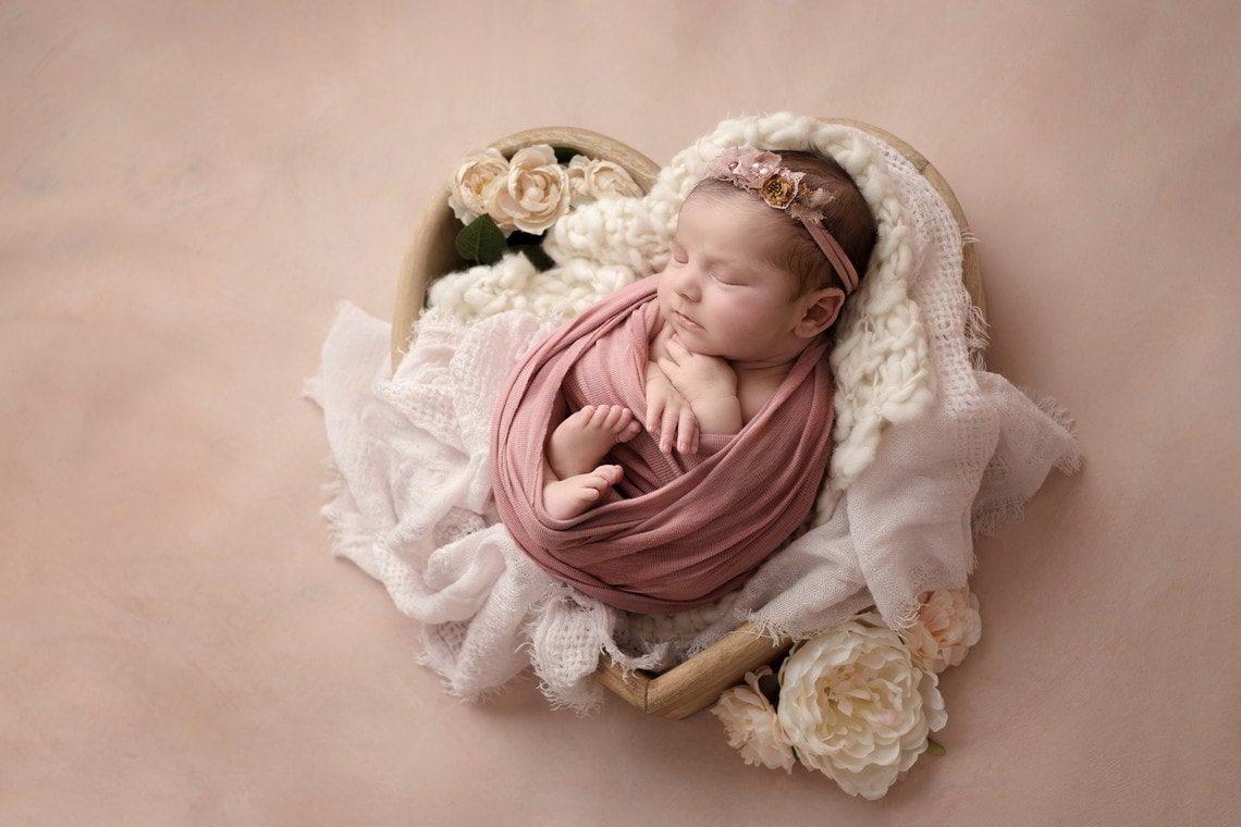 Sur un fond rose, une petite fille nouveau-né est dans un cœur en bois avec des fleurs autour. Elle porte un bandeau fleuri.
