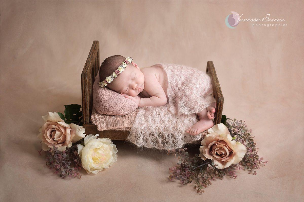 Nouveau-né dans petit lit avec décor fleurs