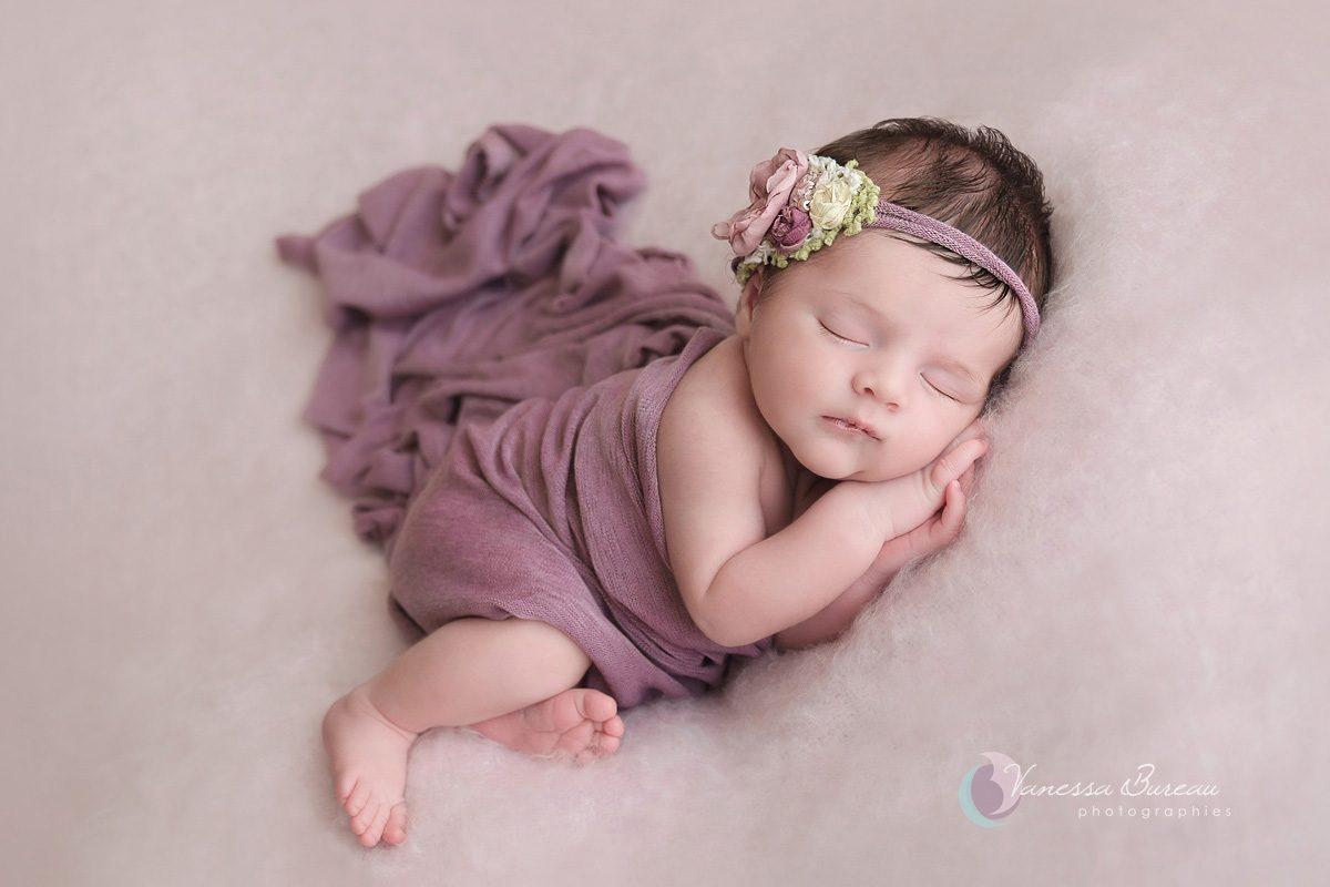 Nouveau-né fille sur plaid rose avec couverture violet