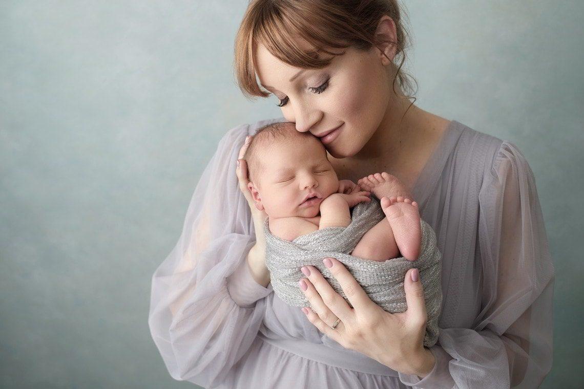 Femme avec son nouveau-né sur fond bleu-vert