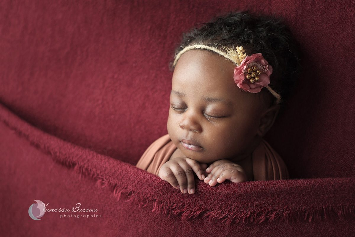 Bébé nouveau-né black sur plaid bordeaux rouge avec fleur