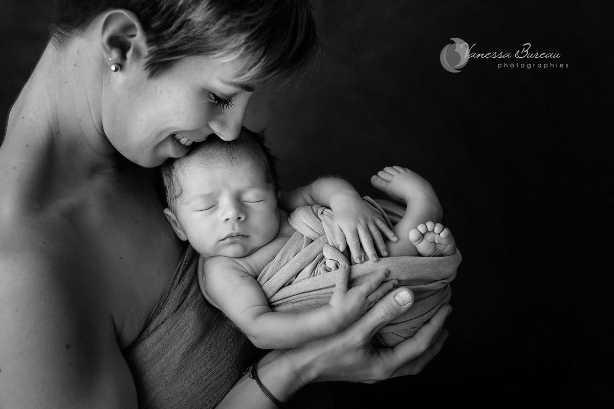 Maman et nouveau-né en position foetale dans un cocon en noir et blanc.
