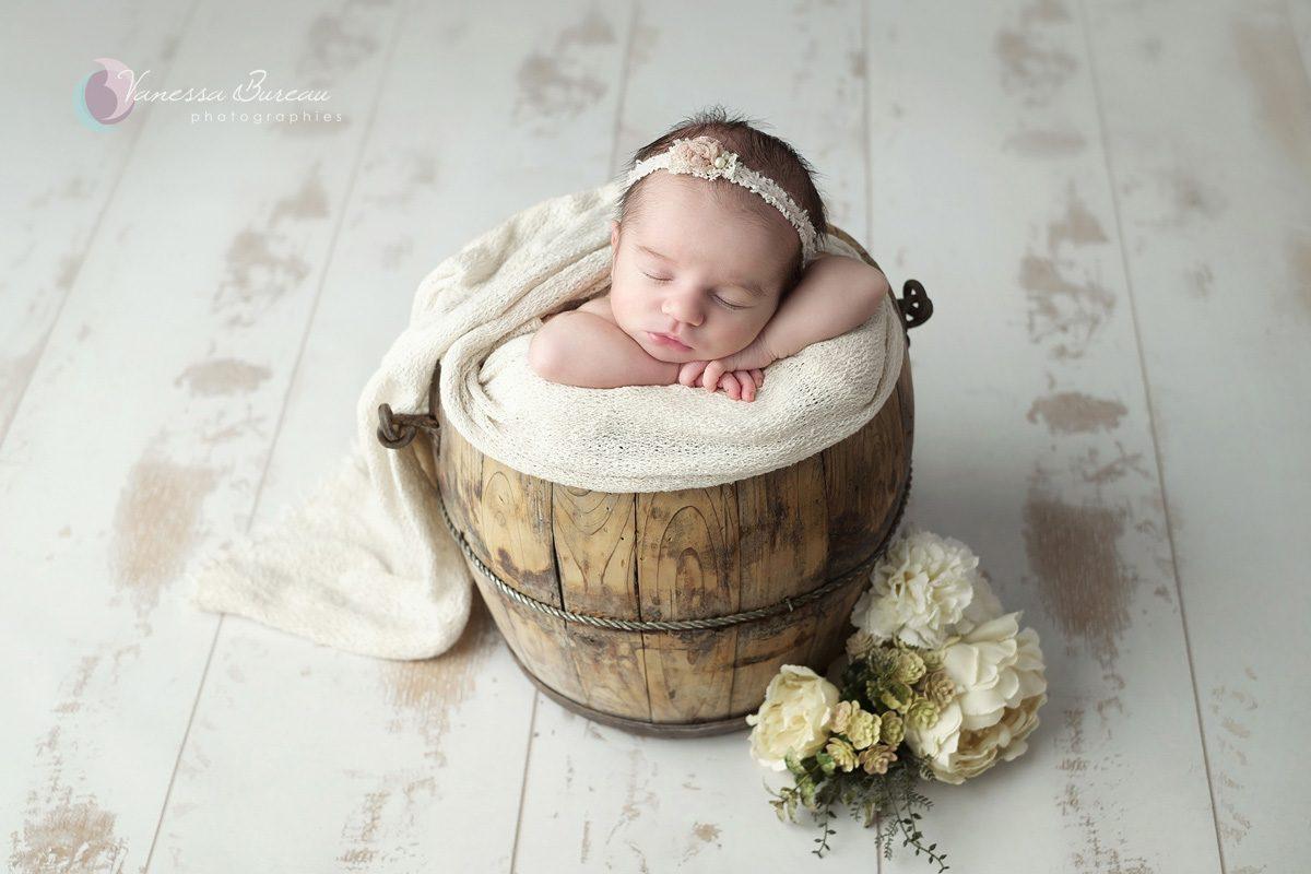 Nouveau-né à Dijon avec des fleurs dans décor beige