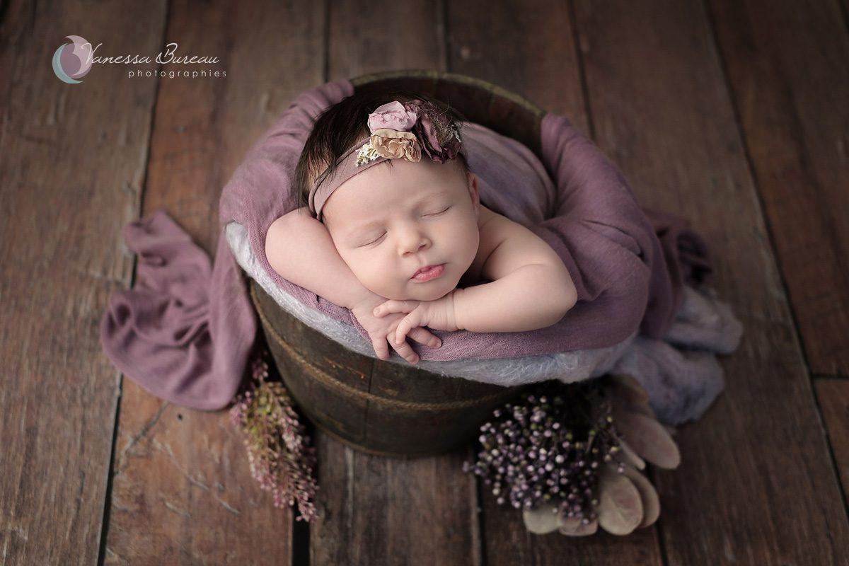 Nouveau-né dans décor végétal violet et brun avec des fleurs