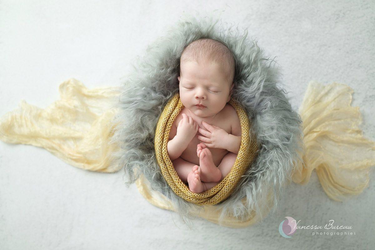 Nouveau-né couverture jaune sur fourrure grise