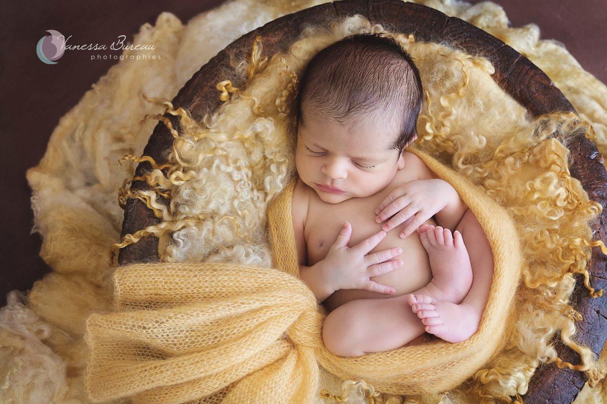 Un nouveau-né est sur le dos en position fœtale, dans un décor en laine jaune et un plancher en bois foncé.