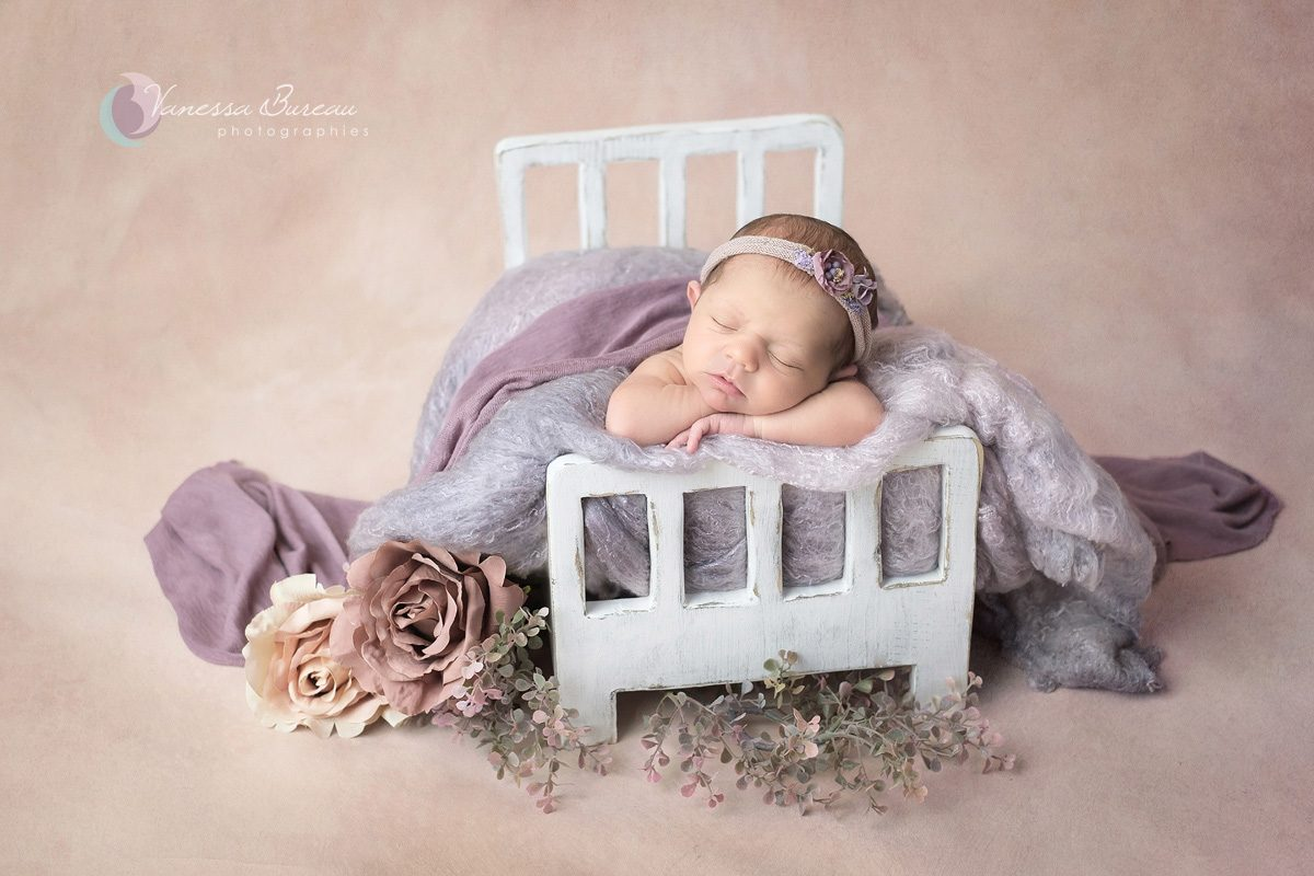 Nouveau-né dans lit blanc avec fleurs