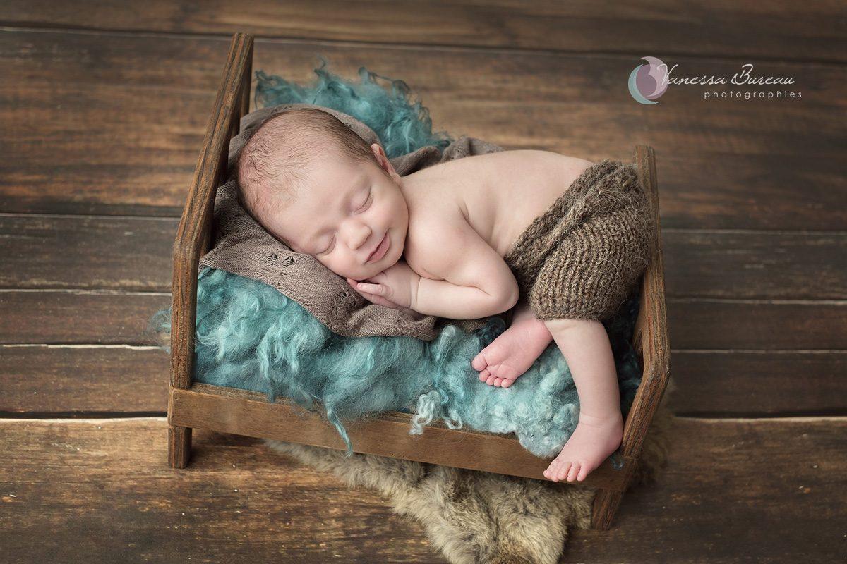 Nouveau-né dans lit en bois et fourrure bleue