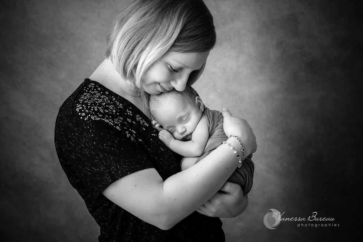 Nouveau-né blotti dans les bras de sa maman, avec tendresse, en noir blanc, dans le studio de la photographe.