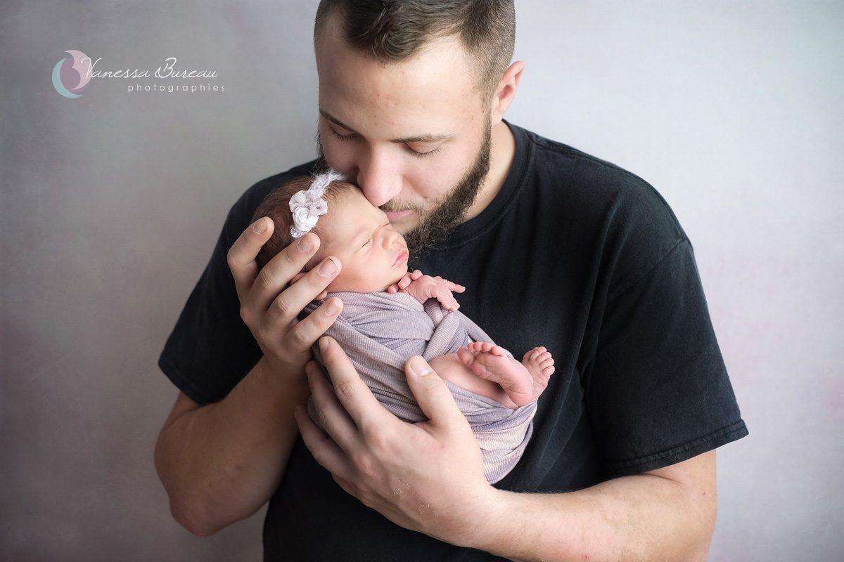 Bisou de papa à son nouveau-né, douceur fond violet
