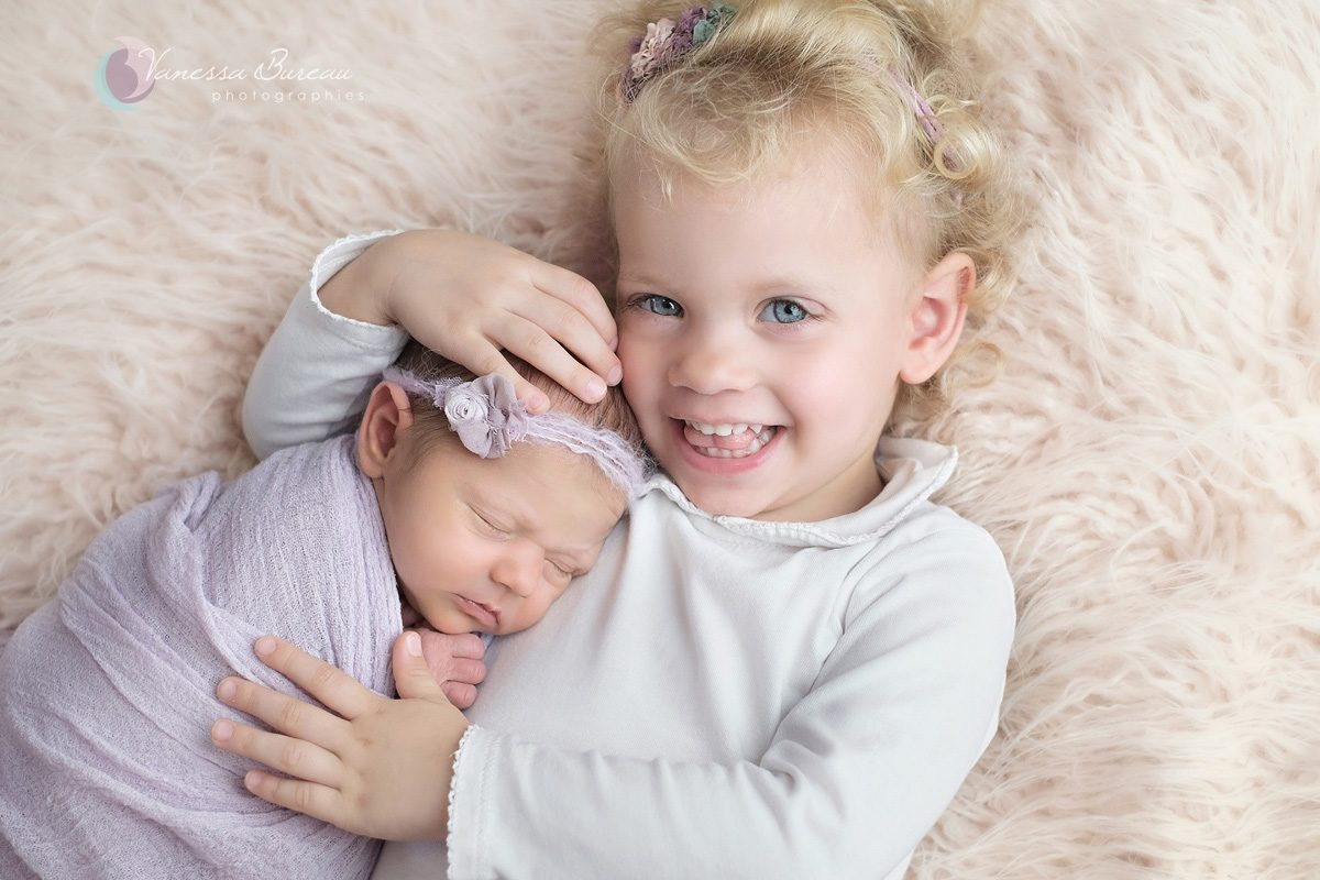 Sourire de grande soeur avec nouveau-né dans ses bras