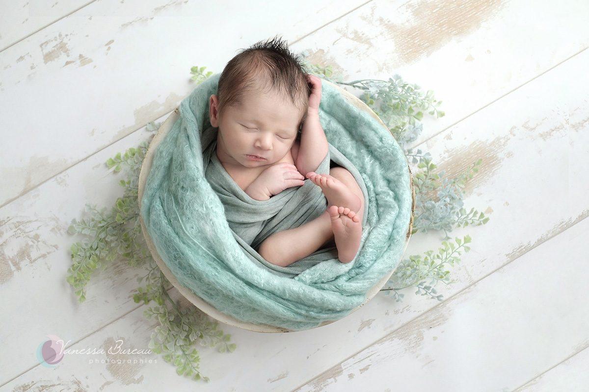 Nouveau-né dans cocon vert d'eau avec feuillage