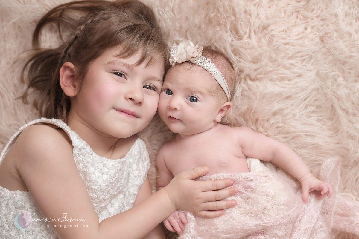 Nouveau-né yeux ouverts avec sa sœur