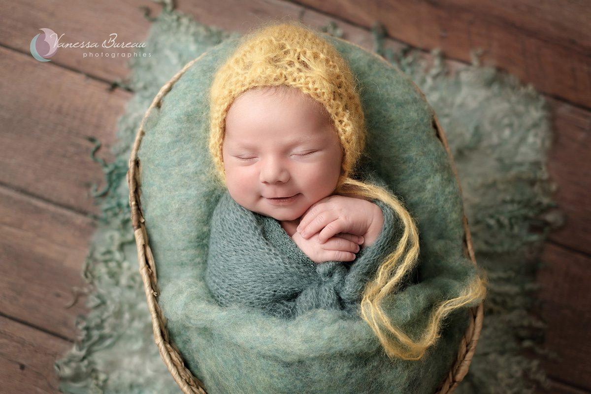 Nouveau-né avec bonnet jaune dans décor vert
