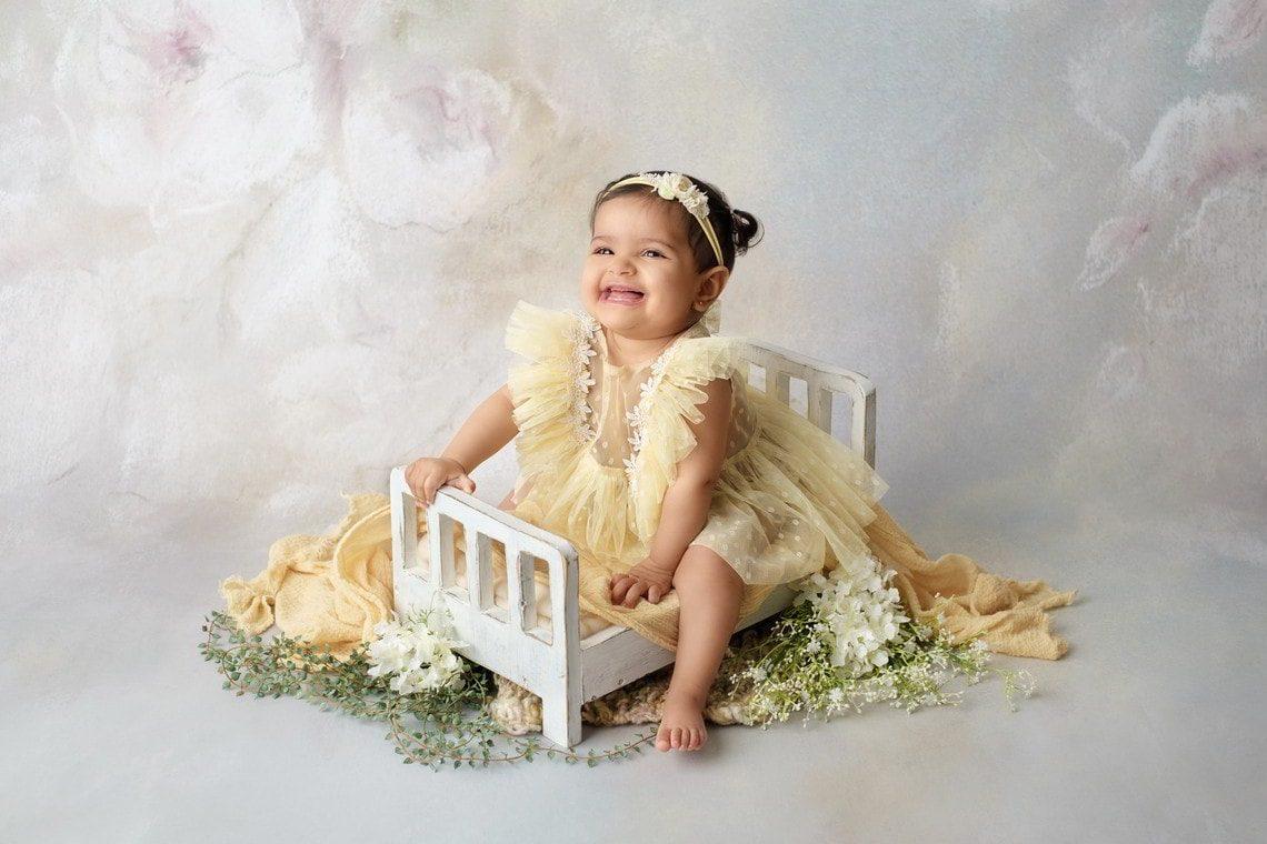 Bébé fille sur lit en bois blanc avec fleurs